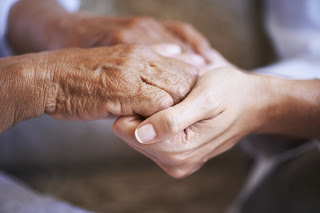Close up of a young caucasian woman's hands holding a senior ethnic woman's hands